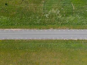 above view photo of a road between graslands