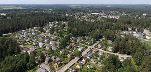 small suburb with trees and roads seen from above
