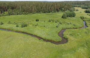 aerial view of a river flowing between meadows