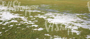 grass field partially covered with snow and ice