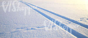 snow covered ground with vehicle tracks