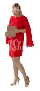 woman in a red dress standing and searching for smth in her purse