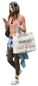 woman carrying a big shopping bag walking and listening to music