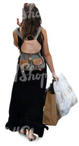 woman in a black summer dress walking and carrying some shopping bags