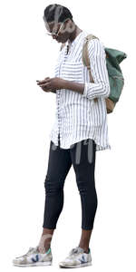 black woman in a striped white shirt standing and looking at her phone