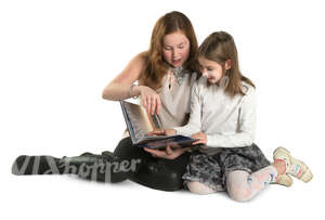 two girls sitting on the ground and reading a book
