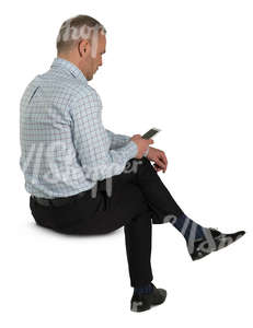 man sitting and looking at his phone