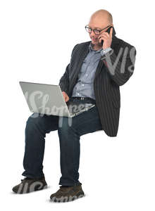 man sitting with a laptop on his knees and working
