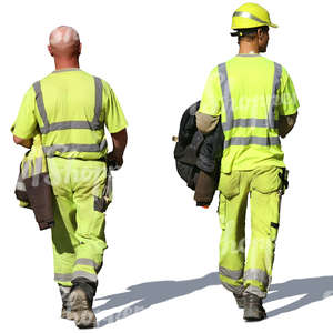 two workmen in work clothes walking in the sunlight