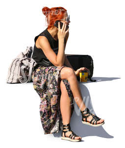 red haired woman sitting and talking on the phone