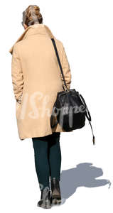 woman in a beige overcoat walking