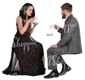 man and woman in fancy clothes sitting in a cafe