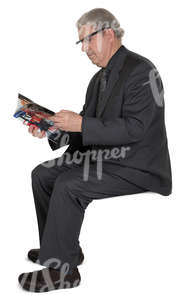 elderly man in a suit sitting and reading a newspaper