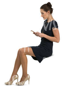woman in a black dress sitting and looking at her phone