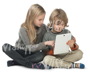 little boy and girl sitting on the floor and looking at ipad