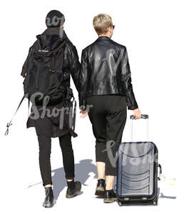 couple in black with travelling bags walking hand in hand