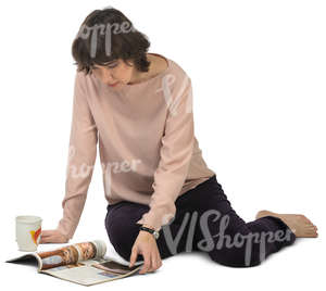 woman sitting on the floor and looking at a magazine