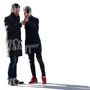 two backlit asian men standing and looking at a phone