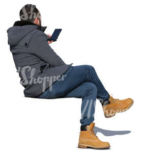 man in a grey autumn coat sitting and looking at his phone