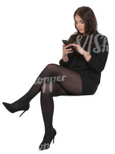 woman in a black costume sitting and texting