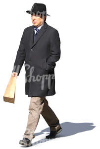 asian man in a black overcoat and hat walking in the sunlight