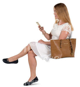 woman in a white dress sitting and texting