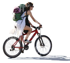 backlit woman with a backpack riding a bike