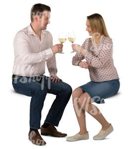 man and woman sitting in a cafe and drinking wine