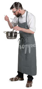 chef standing in the kitchen and tasting soup