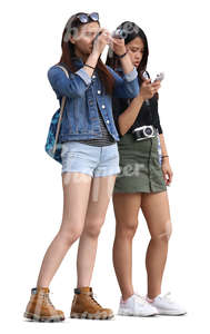 two teenage asian girls standing and taking a picture