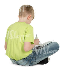 boy sitting on the floor and reading a book