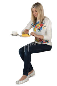 woman sitting in a cafe and eating cake