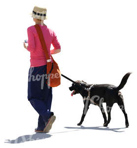 backlit woman walking with a black dog