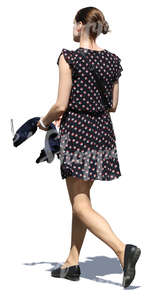 woman in a short summer dress walking in sunlight