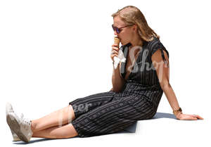 woman sitting on sidewalk and eating ice cream