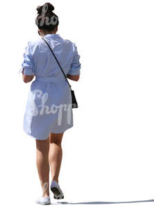 backlit woman on a dress walking on the street