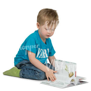young boy sitting onn the floor and reading a book