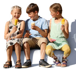 three children sitting and eating ice cream