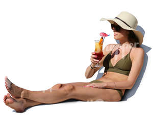 woman in a bikini sitting and drinking cocktail