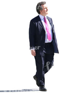 older businessman walking on a sunny day