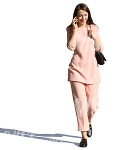 woman in a pink costume walking and talking on the phone