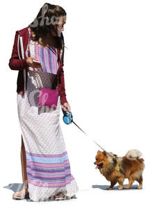 woman in a long summer dress walking a dog