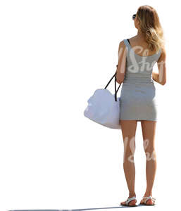 backlit woman in a short summer dress standing