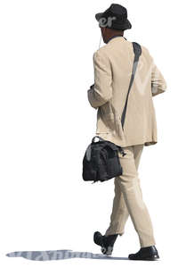 african man in a beige suit walking