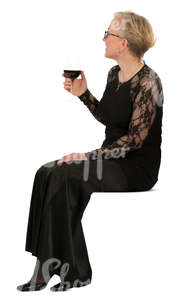 woman in a formal black dress sitting and drinking wine