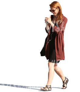 woman walking and looking at her phone