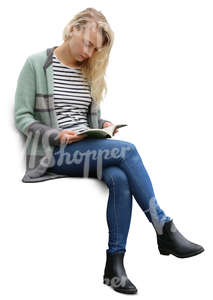 blond woman sitting and reading a book