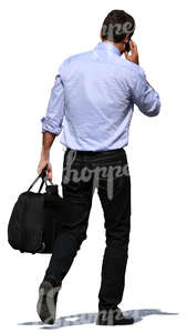 man carrying a bag and talking on a phone
