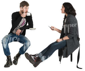 man and woman sitting in a cafe and drinking coffee