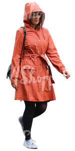 woman in an orange raincoat walking